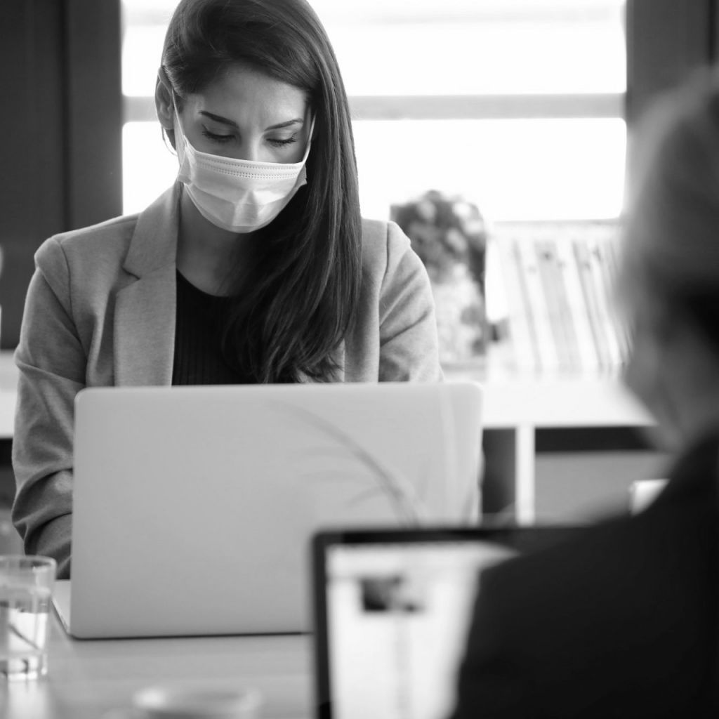 business women wearing a hygienic face mask while work with laptops in the coworking space.
