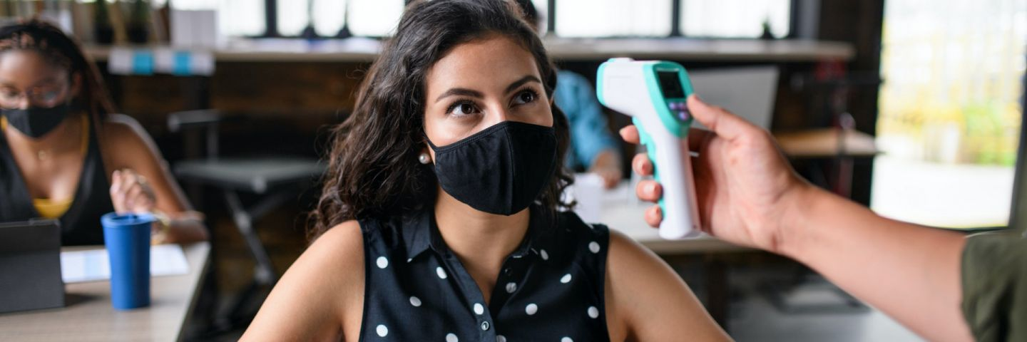 Businesswoman with face mask working indoors in office, measuring temperature